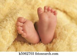 Baby feet on yellow blanket