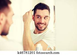 happy man brushing hair with comb at bathroom