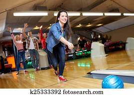 happy young woman throwing ball in bowling club