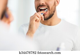 close up of man with toothbrush cleaning teeth