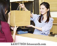 salesclerk handing merchandise to customer