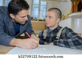 young carpenter trainee learning with mentor