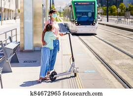 Mother and daughter waiting for the train with an electronic scooter.