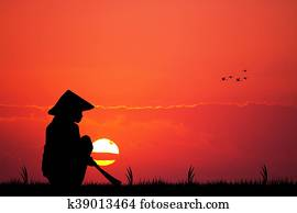 Asian farmer at sunset