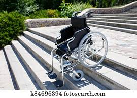 Wheelchair near the steps in a spring park.