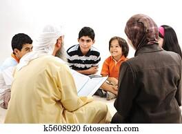 Education activity in Ramadan, Muslim couple and children reading Koran