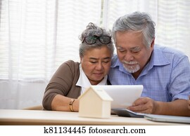 Asian senior couple making sign contract to buy new house, Real estate and loan home finances concept