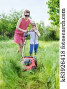 Young woman and her son mowing grass with lawn mower