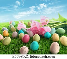 Easter eggs with pink tulips on grass