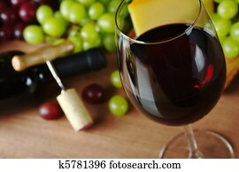 Red wine in wine glass with grapes, cheese a wine bottle and a corkscrew with cork in the background (Selective Focus, Focus on the front of the rim of the wine glass)