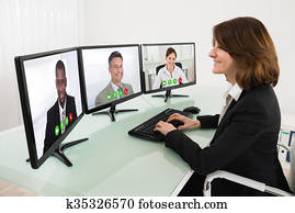 Businesswoman Video Conferencing On Desk