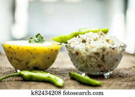 Close up of popular Indian & Asian lunch dish on brown colored surface i.e. Kadhi or Karhi  and kichdi or chawal with fresh green chilies.