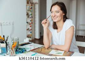 Smiling woman painter holding paintbrush and thinking at the table