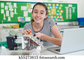 Portrait Of Female Pupil Studying Robotics In Science Lesson