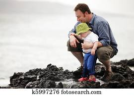 Dad with little son walking outdoors at ocean