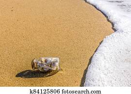 A glass bottle with shells on the seashore in the waves.