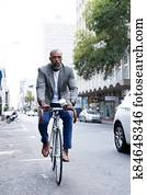 African American business man riding a bike in the street