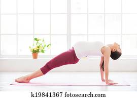 Pre-natal exercise. Beautiful pregnant woman exercising at home