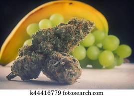 Dried cannabis buds (Grape Ape strain) with fresh fruit - medical marijuana concept