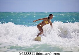 girl in a yellow bikini surfing in Hawaii
