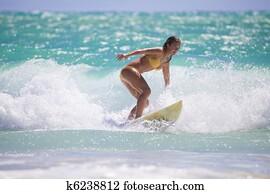 girl in a yellow bikini surfing in Hawaii