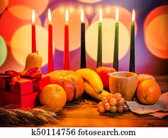Kwanzaa festive concept with seven candles red, black and green, gift box, pumpkin, bowl and fruit on light blur bokeh background
