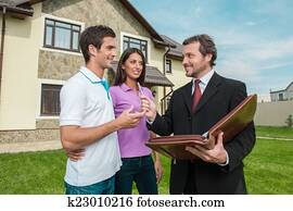 Young couple signing renting contract with real estate agent. agent giving pen to sign agreement for house sale