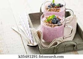 Blueberry smoothie with granola in glass mugs