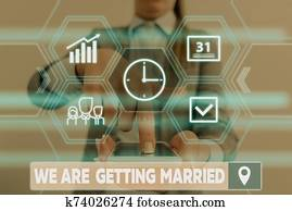 Conceptual hand writing showing We Are Getting Married. Business photo showcasing Engagement Wedding preparation Loving couple Woman wear work suit presenting presentation smart device.