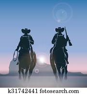 Cowboys silhouettes galloping across the prairie at sunrise