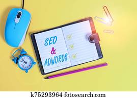 Word writing text Seo And Adwords. Business concept for Pay per click Digital marketing Google Adsense Locked diary sheets clips marker mouse alarm clock colored background.