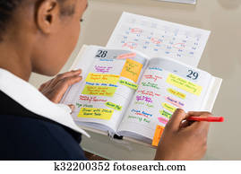 Businesswoman Writing Schedule In Diary