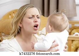 Stressed Mother Holding Baby In Nursery