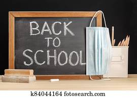 Return to school during covid-19 concept . Chalkboard with handwritten text and face mask hanging on table