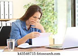 Worried entrepreneur girl reading a letter