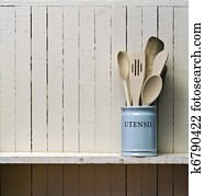 Kitchen cooking utensils; wooden spatulas etc in china storage pot; on wooden shelf against rustic kitchen wall; excellent copy space over wall area