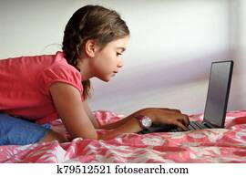 Bored young girl (age 10) using a laptop in bedroom while forced to stay at home because government policies efforts to prevent pandemic coronavirus (COVID-19) spreading