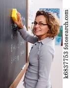 Teacher erasing chalkboard with sponge