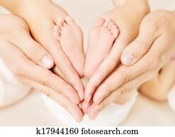 Newborn baby feet in parents hands. Love simbol as heart sign