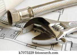Plumbing tools on house blueprint
