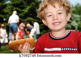 Young boy holding a hot dog at a neighborhood picnic