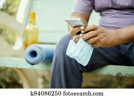 Man using mobile with mask in hand at park during morning yoga or workout with mat - concept of coronavirus or covid-19 advice, protection or to prevent from spreading by wearing mask at outdoor.