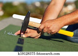 Man hands fastening bitumen roof shingles