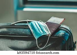 COVID-19 travel mask with luggage. Coronavirus airport restriction. A medical face mask with passport, plane ticket, suitcase and luggages