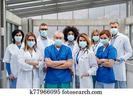 Group of doctors with face masks looking at camera, corona virus concept.