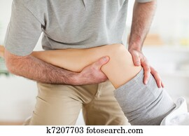 Chiropractor massaging a woman's knee