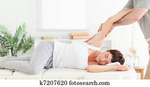 Chiropractor stretching woman's arm