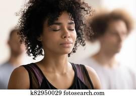 Young peaceful african american woman enjoying deep meditation.