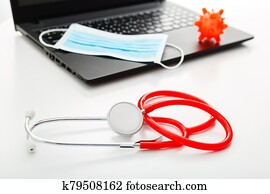 Red Stethoscope, surgical protective mask, model of coronavirus Microscope virus on laptop. Coronavirus covid-19 covid19 prevention. Medicine health care concept. Doctors workplace, doctors appointment