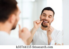 man with dental floss cleaning teeth at bathroom